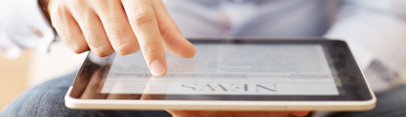 A man is reading news on an electronic mobile device or tablet.