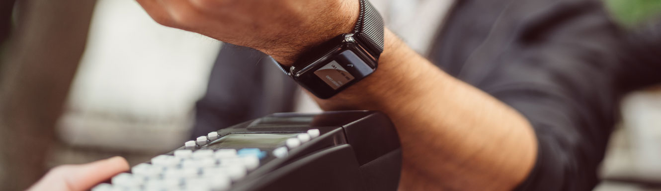 A man is using Mobile Wallet with his smartwatch to make a purchase.