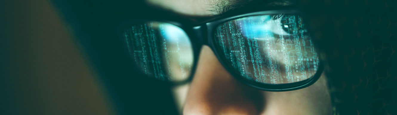 A closeup of a computer hacker with a computer screen reflecting in his eye glasses.
