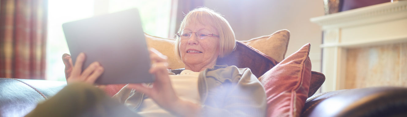 A woman sits on her couch smiling and using her electronic tablet.