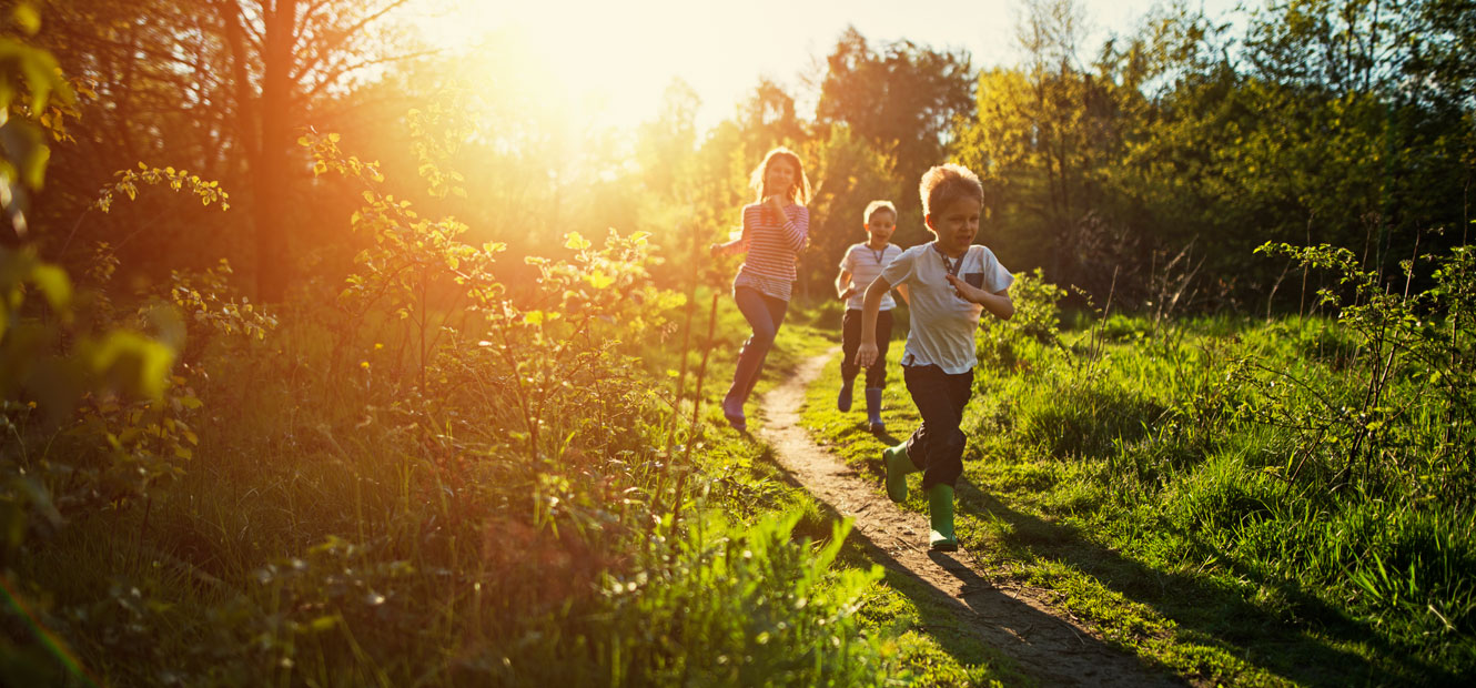 Three children run on an outdoor path surrounded by trees and tall grasses.