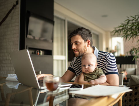 A dad holds his baby boy while sitting at the dining room table and working on his laptop.