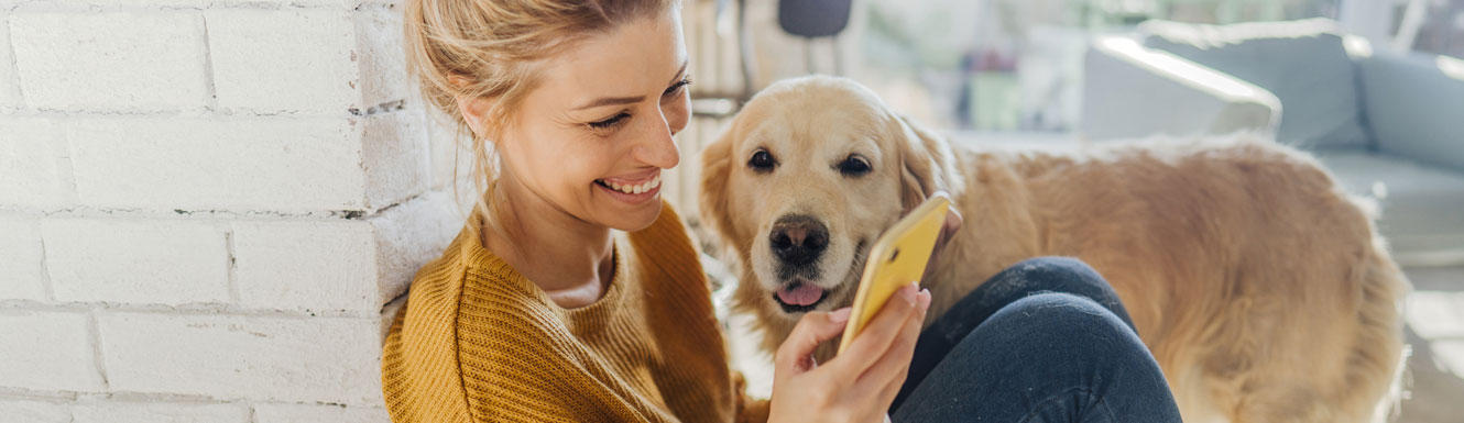 A woman sits on the floor smiling and looking at her cellphone with her Golden Retriever dog nearby.