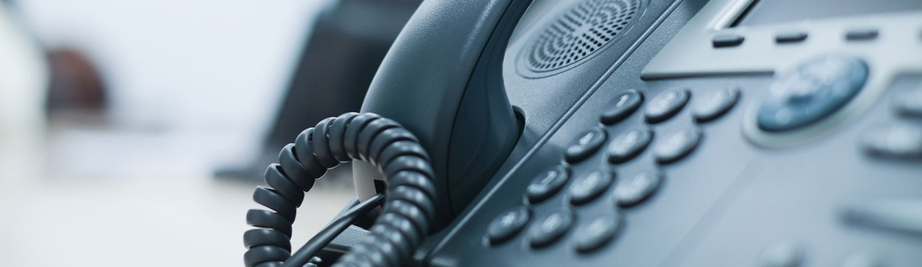 A black business telephone is pictured with a blurry background.