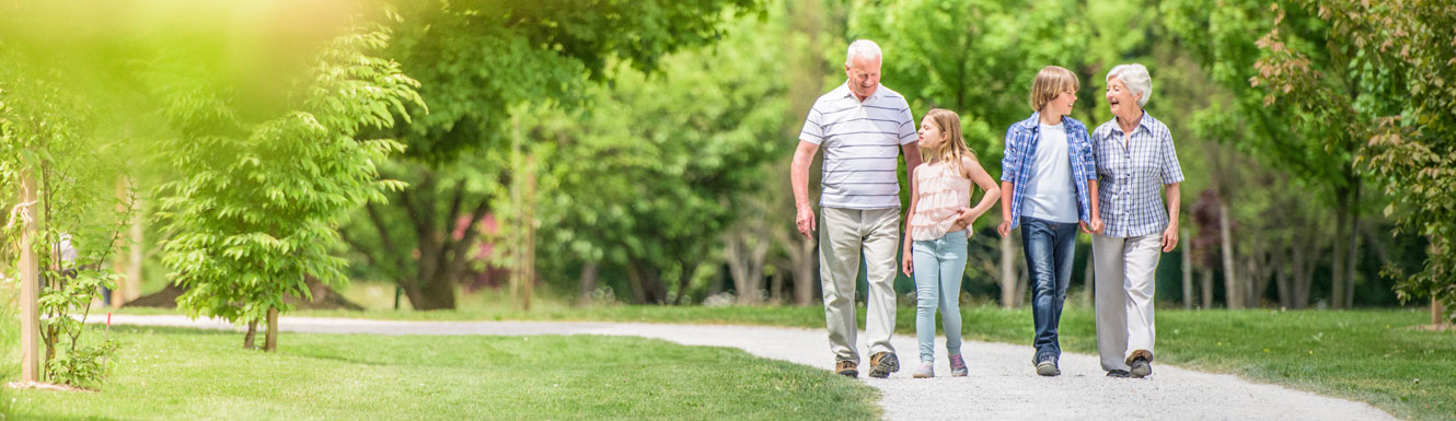 Two grandparents are walking with their young grandchildren on a path surrounded by grass and trees.